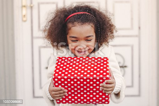 Cute girl in front of house with gift