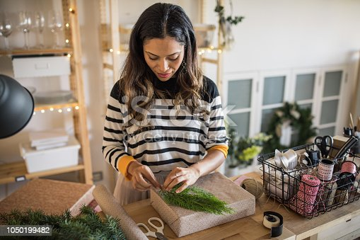 Woman wrapping Christmas present at gift shop. She wearing casual clothing