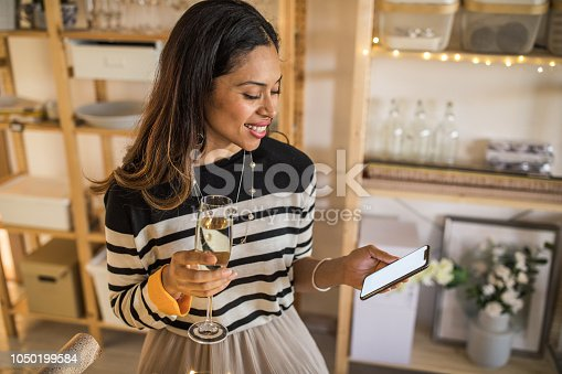 Woman wrapping Christmas present at gift shop. She wearing casual clothing, drinking wine and use mobile phone to check social networks