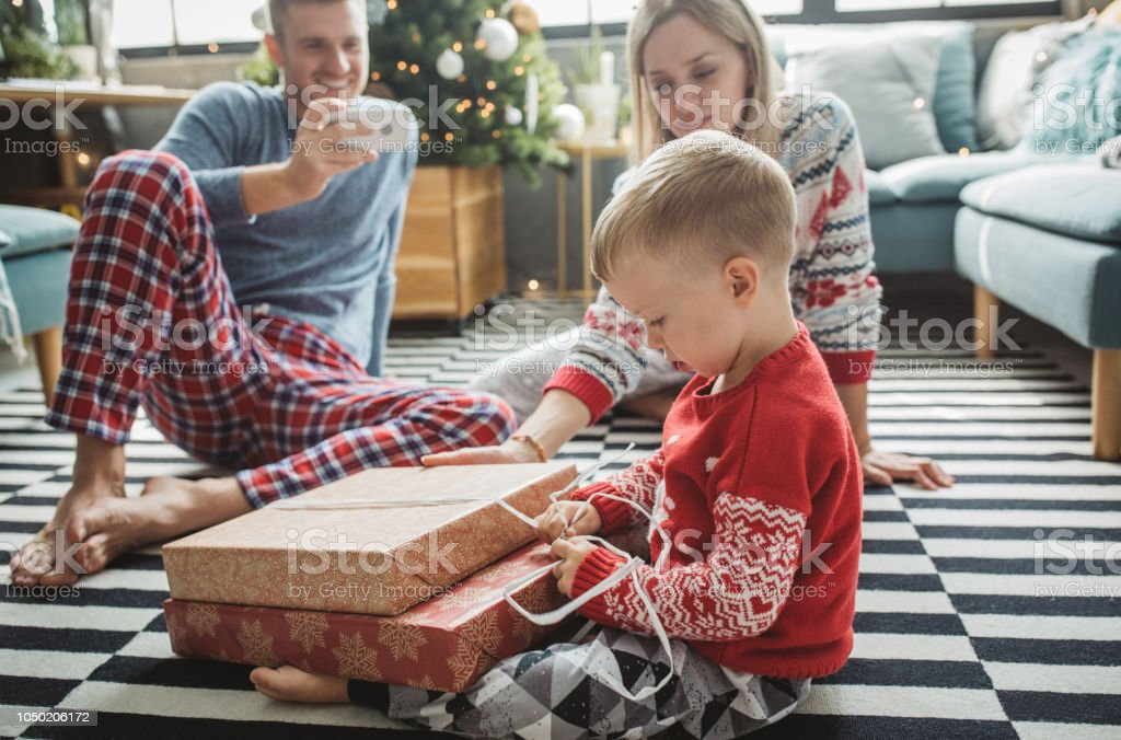 Young parents with baby boy celebrating Christmas at home, boy...