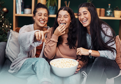 Shot of young sisters having popcorn and watching tv together during Christmas at home