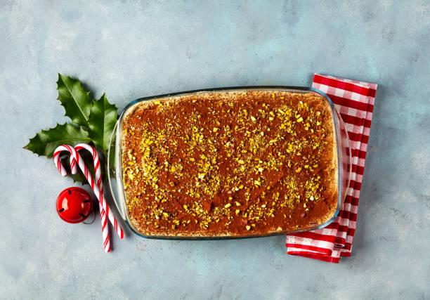 weihnachten italienische klassische tiramisu kaffee-dessert mit pistazien, savoiardi und kakao creme auf a blaue tabelle. silvester stil. blätter der stechpalme und dekorative spielzeug, beulen. - weihnachtlich tiramisu stock-fotos und bilder