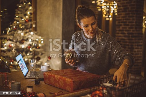Woman wrapping gifts for Christmas at home.