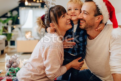 Photo of a cute little family enjoying together the jolliest time of the year - Christmas