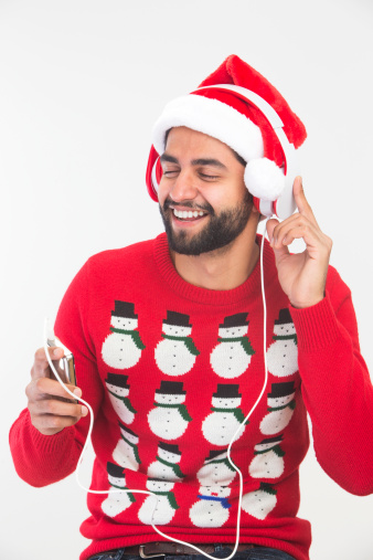 Asian man smiles while wearing a novelty christmas sweater, santa hat and headphones and listening to something on an mp3 player.