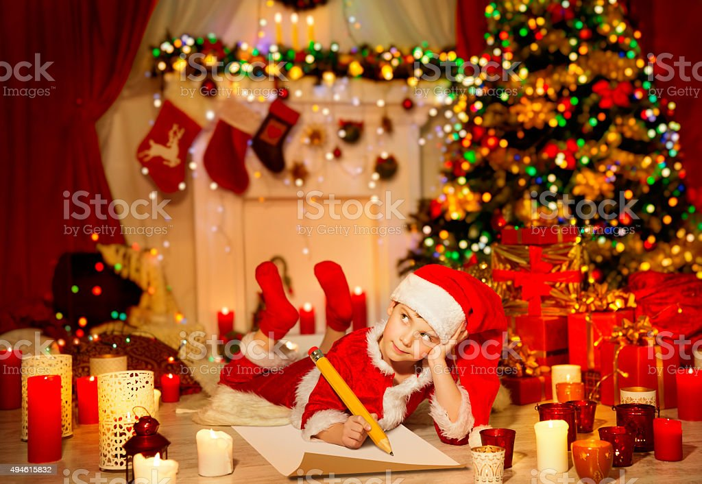 Christmas Kid Write Wish List, Child Santa Hat Writing Letter stock photo