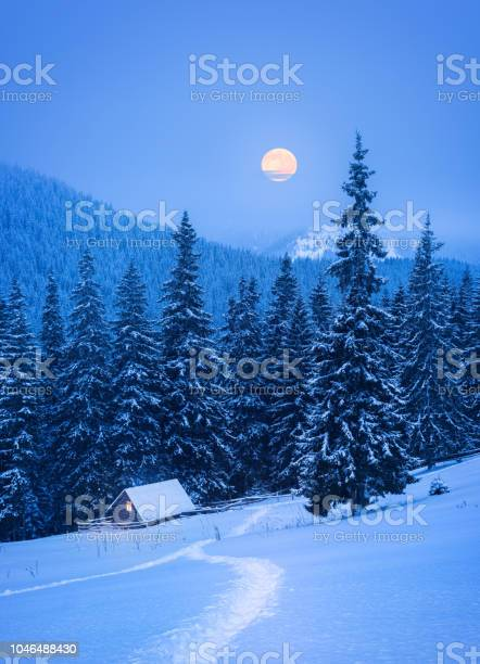 Photo of Christmas landscape with a house in the mountains