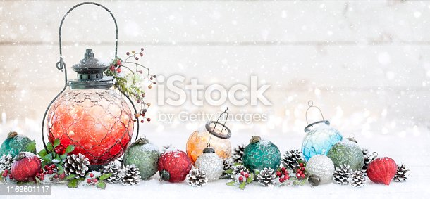 Christmas lantern and baubles background with defocused lights on old white rustic wood