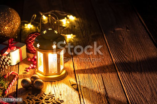 Christmas lantern candlelight beams, gifts and baubles on old rustic wooden table