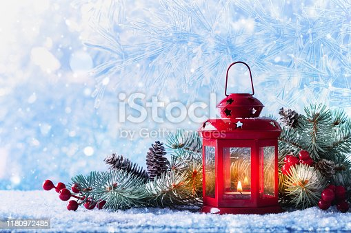 istock Christmas lantern in snow with fir tree branch. Winter cozy scene for New Year holidays. 1180972485