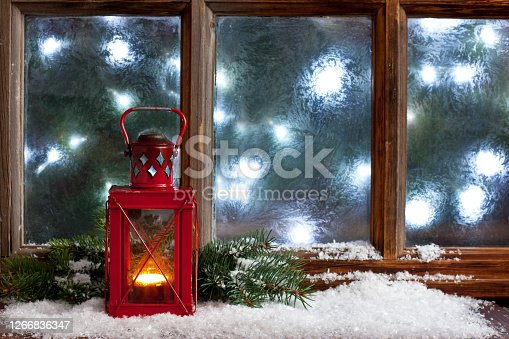 Frosted window with burning lantern. Christmas greeting card. Atmospheric photography. Christmas night
