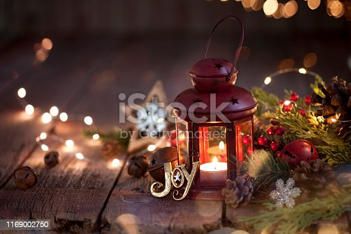 Christmas garland wreath with a red lantern on old wood background and defocused lights