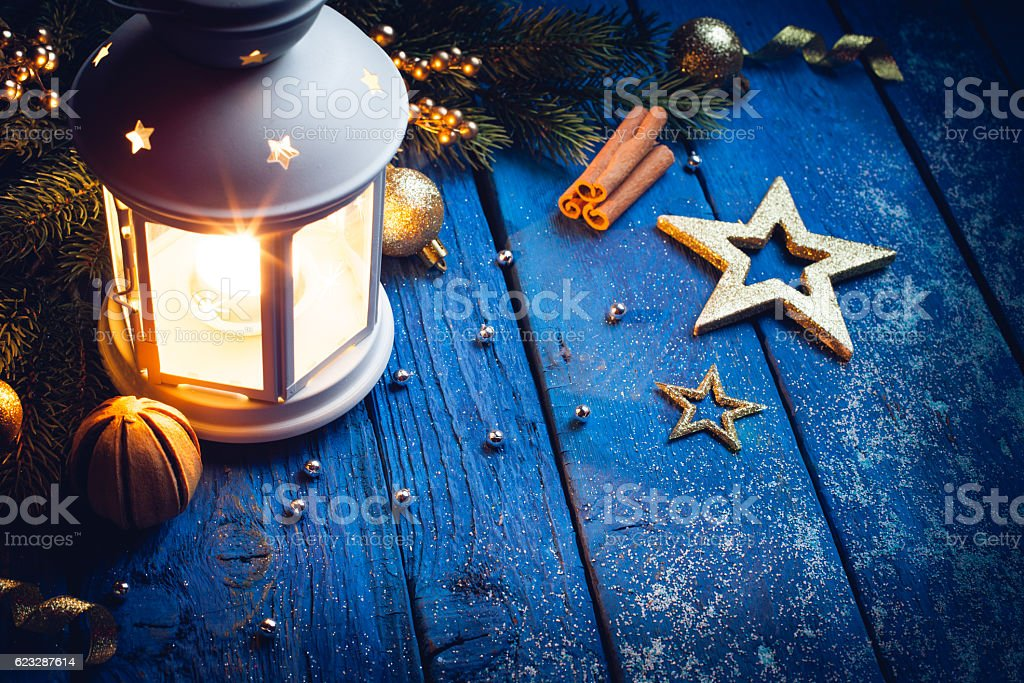 Christmas Lantern with decorations on blue wooden background stock photo