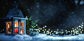 Christmas lantern on snow and fir branch. Evening scene with dark sky and defocused lights in the background