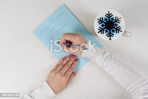 1062609644istockphoto Christmas letter - congratulations. Cup with hot tea and a symbolic snowflake 981644148