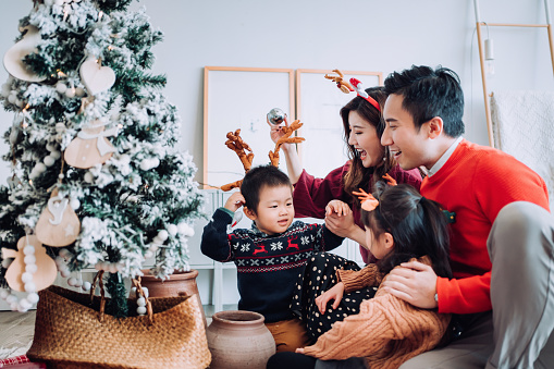 Christmas lifestyle theme. Happy Asian family decorating Christmas tree together in the living room at home. They are putting on various baubles and ornaments and enjoying their holiday