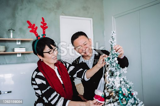 Christmas lifestyle theme. Senior Asian couple decorating a Christmas tree together in the living room at home. They are putting on various baubles and ornaments and enjoying their holiday