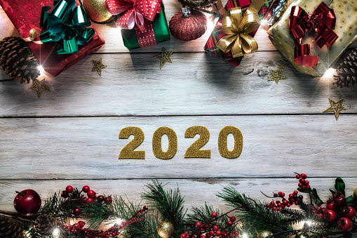 Christmas lights and decoration with gifts making a frame. Year 2020 sign. Christmas themes.