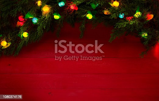 Christmas lights and pine tree on red wood background
