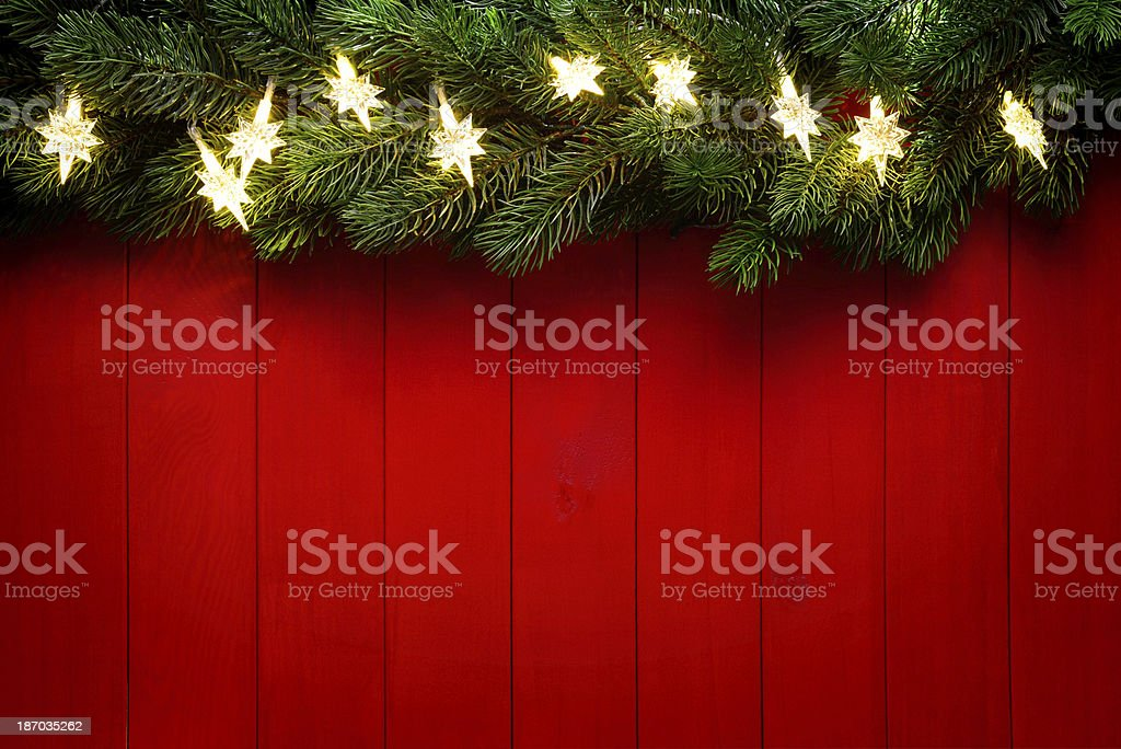 Christmas lights and pine tree on red wood background royalty-free stock photo