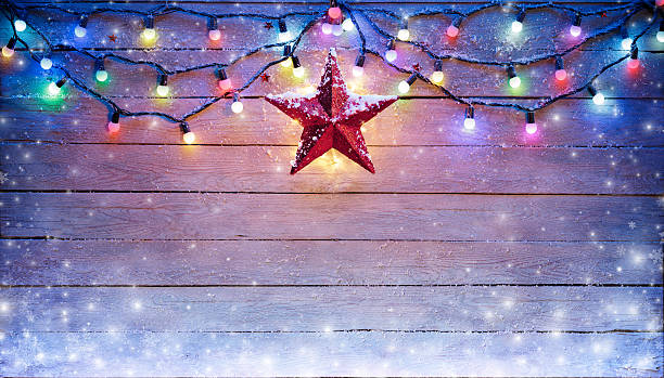 christmas lights and star hanging on snowy plank - illumination photos et images de collection