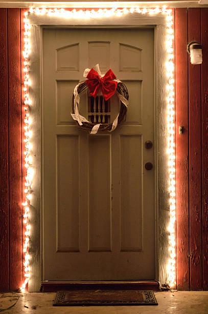 christmas lights and wreath on front door at night - deko hauseingang weihnachten stock-fotos und bilder