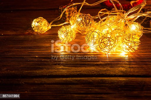 istock Christmas lights decoration on brown wooden background 857441994