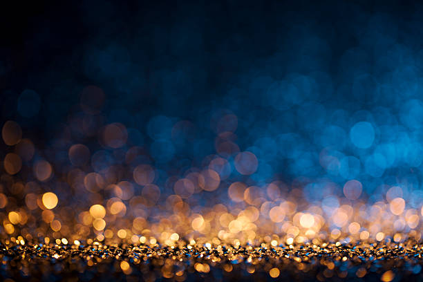 christmas lights defocused background - bokeh gold blue - goldener glitzer stock-fotos und bilder