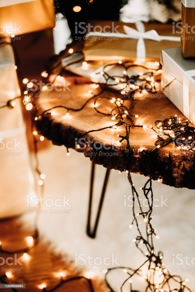 Christmas lights details, presents and gift packages on wooden table...