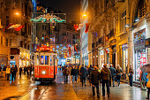 Illuminated Tramway on a rainy Istiklal Avenue (Independence Avenue), Lots of national flags for the Republic Day. iStockalypse.