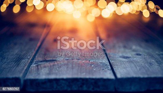 istock Christmas lights on empty table - Background Defocused Blue wood 627683252