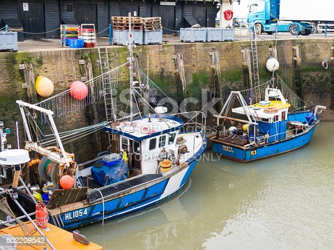 Whitstable, UK - December 19, 2015:  Two fishing boats in Whitstable harbour, Kent, celebrate christmas by hanging christmas fairy lights on their rigging.