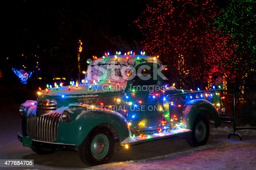 Littleton, United States - December 21, 2013: The Christmas season is celebrated on entire landscapes.  Here an old Chevy truck is decked out in Christmas lights on a ranch filled with lighted trees in the background.