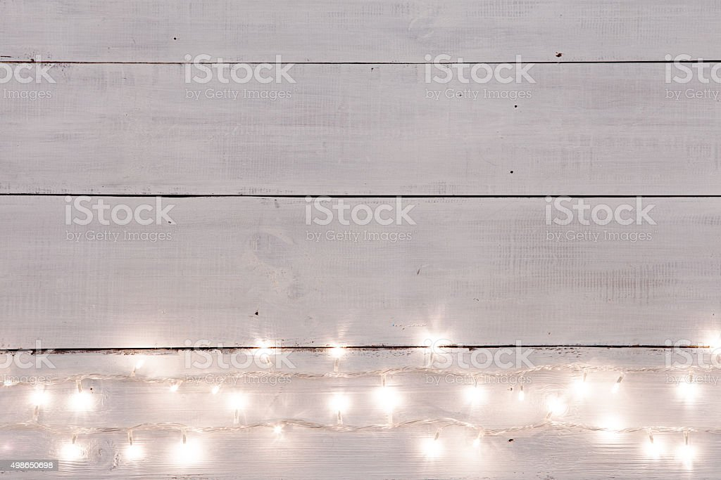 Christmas lights on white painted wooden background stock photo