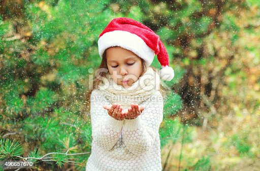 istock Christmas little child in santa red hat blowing on snow 496657670