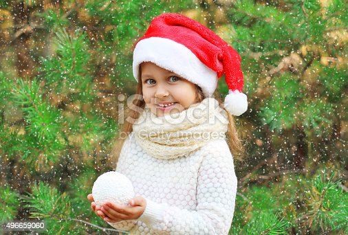 istock Christmas little child in santa red hat with snowball 496659060