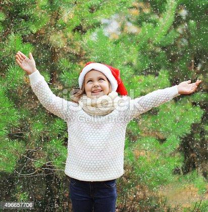 istock Christmas little girl child in santa red hat enjoying snow 496657706