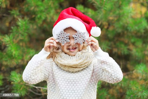istock Christmas little girl child in santa red hat with snowflakes 496657788