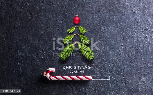 istock Christmas Loading Concept - Tree And Candy Canes On Black Stone 1181847174