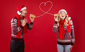 Christmas love message. Cute couple in Santa hats and sweaters talking on tin phone over red background, panorama