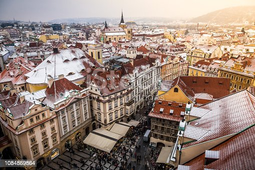 Color image depicting a high angle view of the rooftops and old architecture of Prague old town in Czech Republic. In the town square below people and tourists are browing the many stalls of the Christmas market. Image shot on a cold winter's day. Room for copy space.