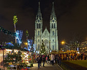Prague, Czech Republic - December 5, 2017: Christmas market at Namesti Miru (Peace Square) in front of St. Ludmila Church in night. Unknown people walk around the market stalls. Traditionally, it is the first Christmas market of the season.