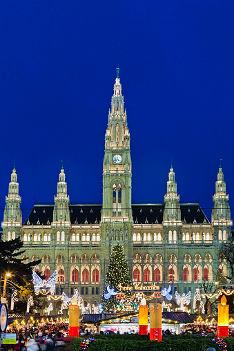 Vienna, Austria - December 12, 2010: usual evening crowd at the Christkindlmarkt in the Rathausplatz, the most important Christmas Market among the numerous of the city. In the background stands the imposing Vienna City Hall, a beautiful example of Gothic Revival architecture.