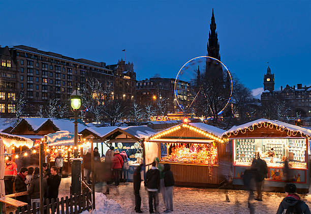 Christmas Market in Central Edinburgh Edinburgh, Scotland - 1st December 2010: Shoppers visiting traditional wooden stalls at a public Christmas market situated next to Princes Street in the city centre of Edinburgh, with Jenners department store, the Scott Monument and the Balmoral Hotel visible on the skyline. princes street edinburgh stock pictures, royalty-free photos & images