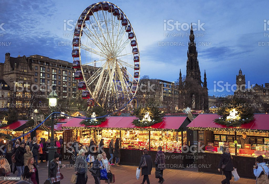 Christmas Market in Edinburgh, Scotland Edinburgh, Scotland, UK - December 11, 2013: People visiting the Christmas markets in Edinburgh's city centre, with a ferris wheel ride and the Scott Monument in the background. Capital Cities Stock Photo