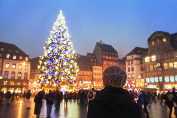 christmas market in Europe people in christmas market, woman looking at the decorated illuminated tree, festive new year lights in Strasbourg, France, Europe strasbourg stock pictures, royalty-free photos & images