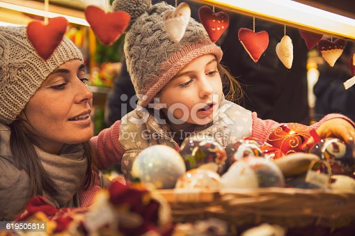 mother and daughter selecting decoration on a Christmas market - retro look vinatge