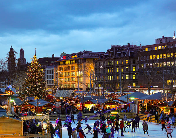 Christmas market zuerich city iceskating christmas market in zuerich at dawn. market huts and an icefield for iceskating. picture taken from the opera house in december 2015. In the background is the typical skyline of zuerich. zurich stock pictures, royalty-free photos & images