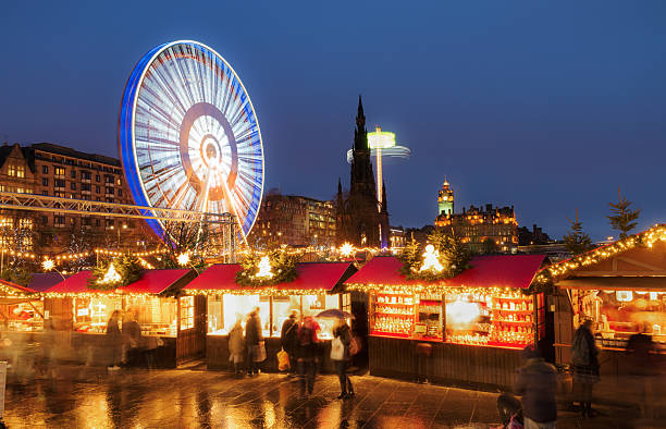 Christmas markets and amusement rides in central Edinburgh, Scotland People browsing winter market stalls, just off Princes Street in Edinburgh's city centre during the run-up to Christmas and Hogmanay, the city's famous New Year's celebrations. princes street edinburgh stock pictures, royalty-free photos & images