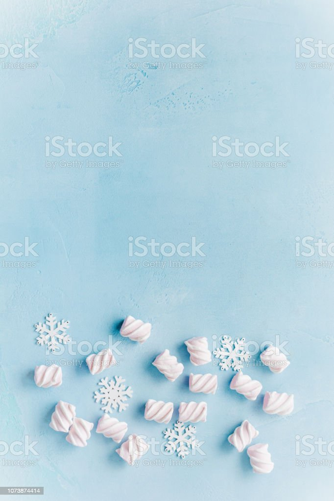Christmas marshmallows and snowflakes on a blue concrete background.Top view. stock photo